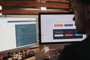 Man sitter framför dataskärm och arbetar med kod